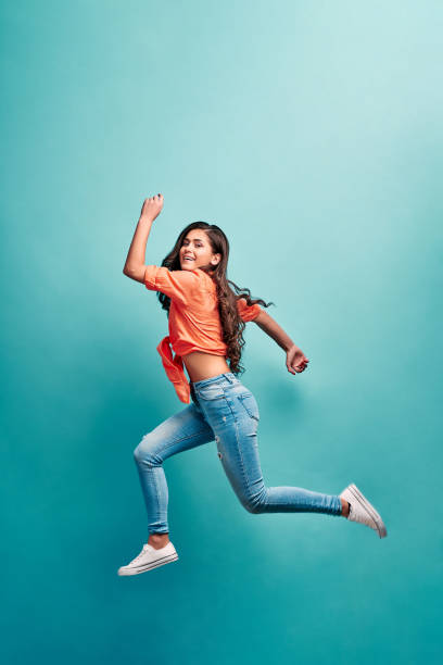 Beautiful young attractive careless girl jumping having fun fooling flying isolated on bright vivid turquoise color background. Concept of carefree and cheerful mood.Full length body size view. stock photo