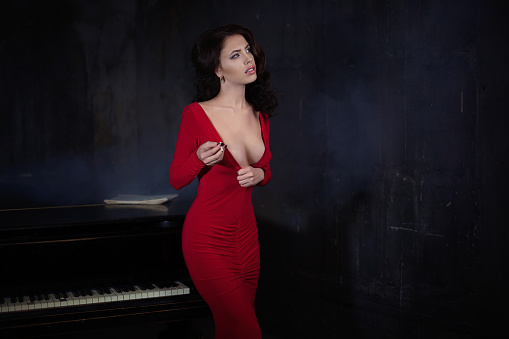 beautiful young attractive woman in evening red dress and piano