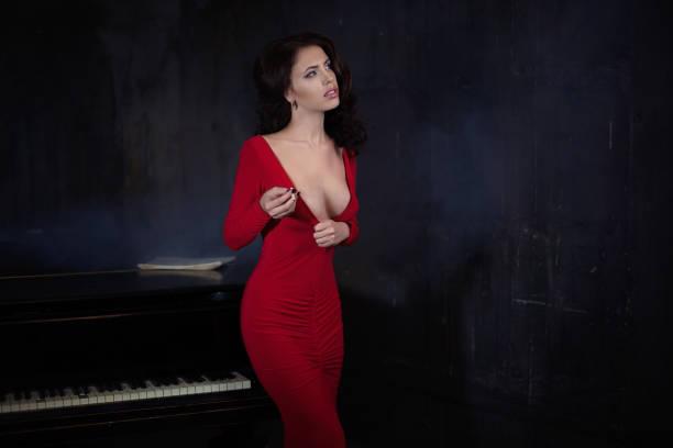 belle jeune femme attrayante en piano et robe rouge de soirée - Photo