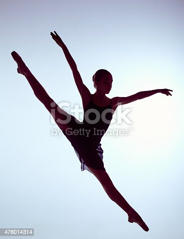 istock Beautiful young ballet dancer jumping on a gray background 476014314