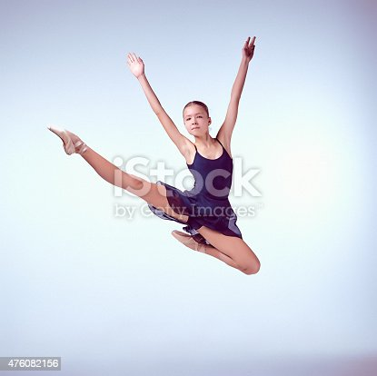 istock Beautiful young ballet dancer jumping on a gray background 476082156
