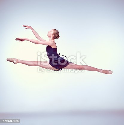 istock Beautiful young ballet dancer jumping on a gray background 476082160