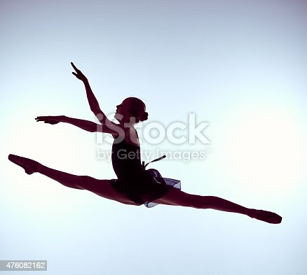 istock Beautiful young ballet dancer jumping on a gray background 476082162