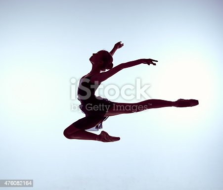 476021886 istock photo Beautiful young ballet dancer jumping on a gray background 476082164