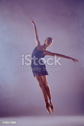 476021886 istock photo Beautiful young ballet dancer jumping on a lilac background 476021858