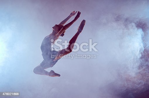 476021886 istock photo Beautiful young ballet dancer jumping on a lilac background 476021866