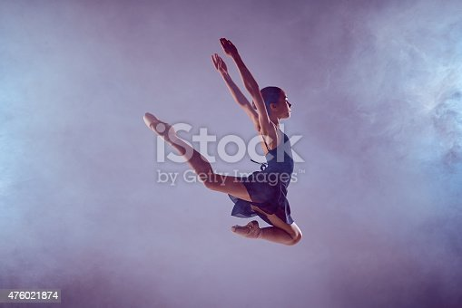 476021886 istock photo Beautiful young ballet dancer jumping on a lilac background 476021874