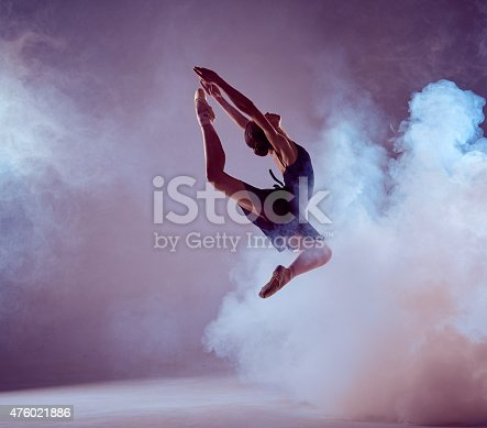 istock Beautiful young ballet dancer jumping on a lilac background 476021886