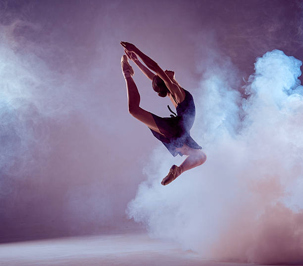 Beautiful young ballet dancer jumping on a lilac background young ballet dancer jumping on a lilac background. Ballerina is wearing in blue dress and pointe shoes. The outline shooting - silhouette of girl with smoke effect performance stock pictures, royalty-free photos & images