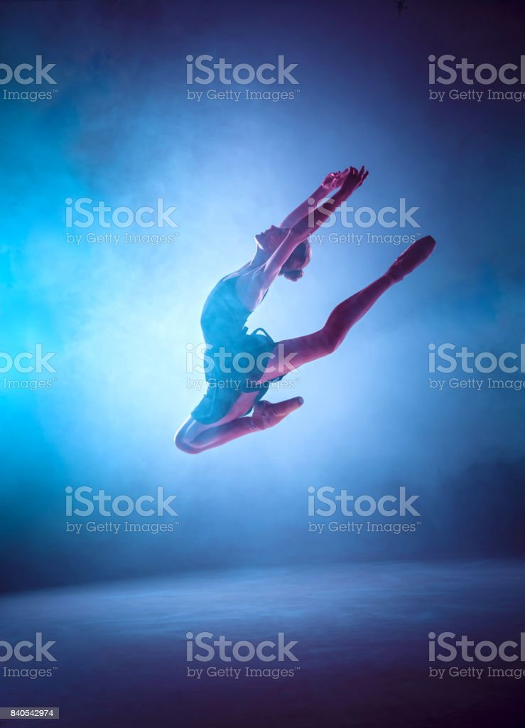 Beautiful young ballet dancer jumping on a lilac background stock photo