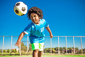 A young black boy child playing soccer on a neighbourhood football pitch on a beautiful sunny day in the Netherlands