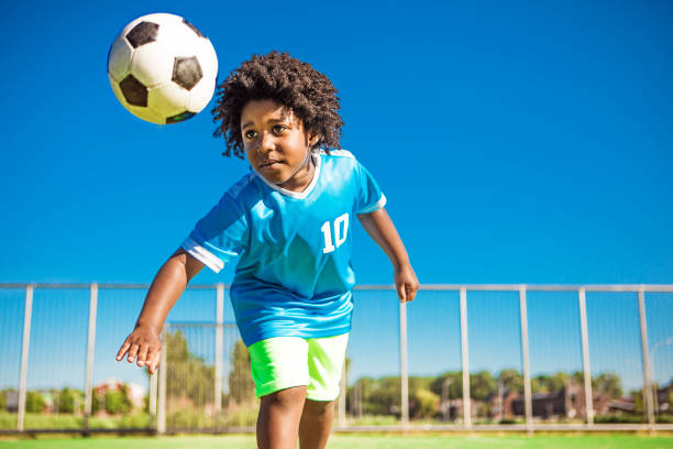 Beautiful young black boy training on the football pitch stock photo