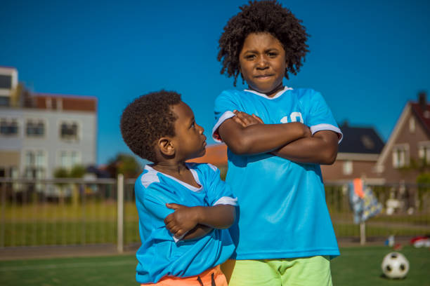 Beautiful young black boys training on the football pitch stock photo