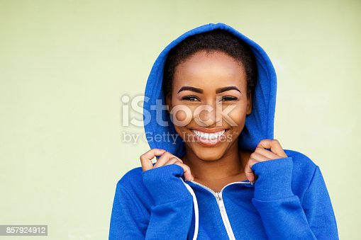 istock beautiful young black fashion woman smiling against green wall 857924912