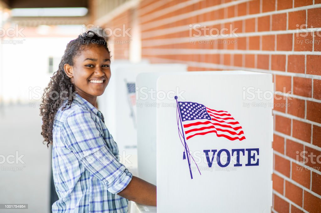 Beautiful Young Black Girl Voting A young black girl voting on election day 18-19 Years Stock Photo