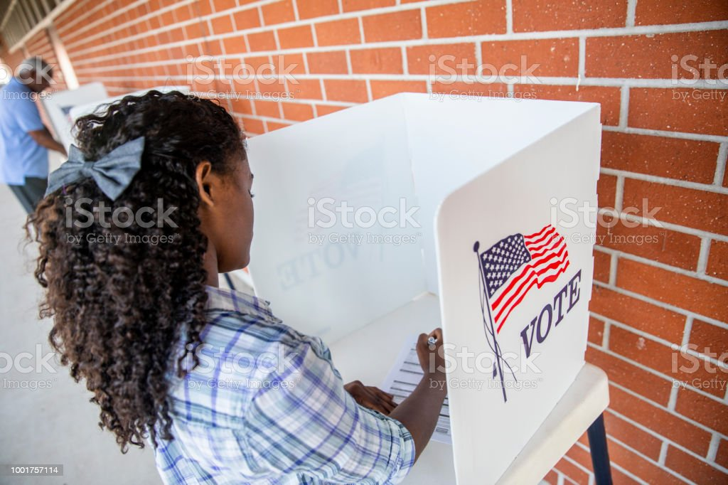 A young black girl voting on election day