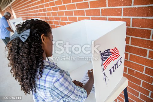 1001757174 istock photo Beautiful Young Black Girl Voting 1001757114