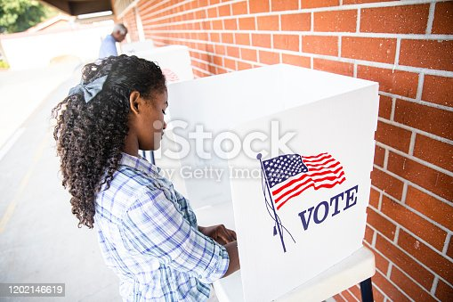 1001754954 istock photo Beautiful Young Black Girl Voting 1202146619