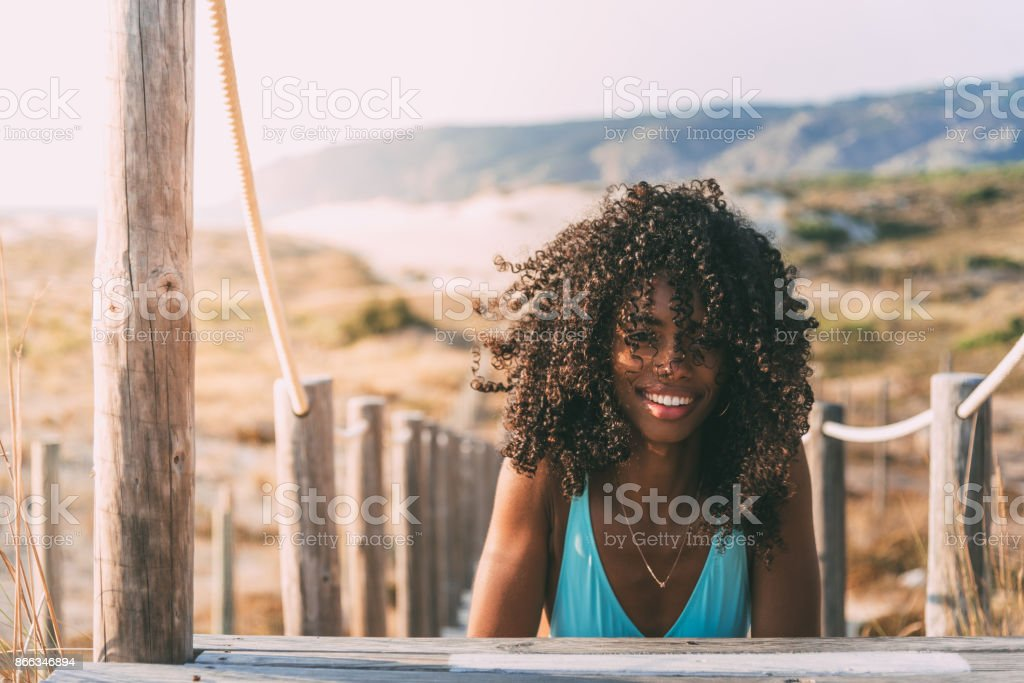 Beautiful young black woman lying down in a  wooden foot bridge at the beach stock photo