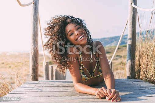 istock Beautiful young black woman lying down in a  wooden foot bridge at the beach 866346950