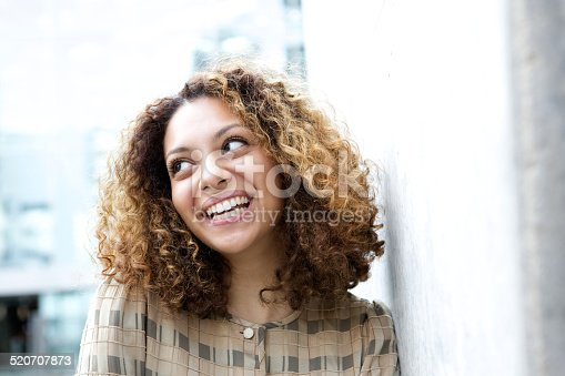 istock Beautiful young black woman smiling outdoors 520707873