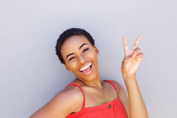 beautiful young black woman smiling with peace hand sign stock photo