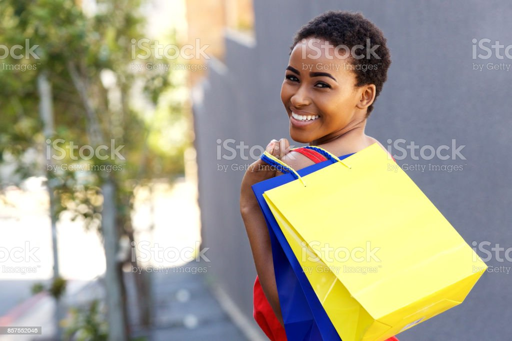 beautiful young black woman smiling with shopping bags outside stock photo