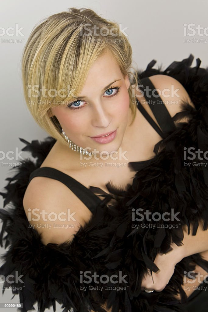 Beautiful Young Blond Woman In Black Dress and Feather Boa stock photo