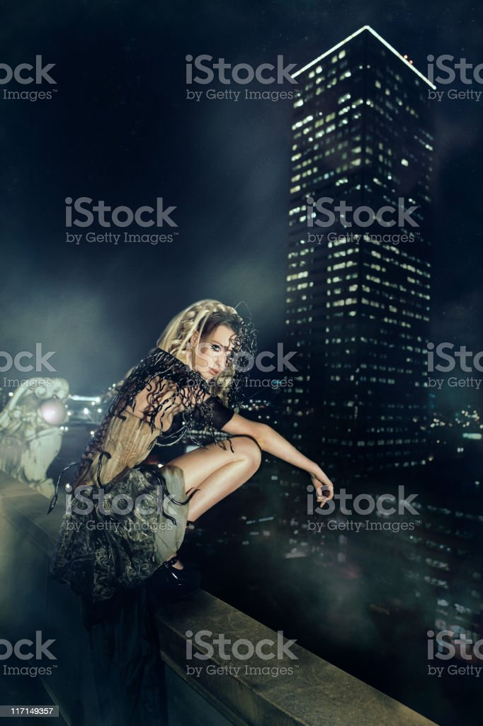Beautiful Young Woman Fashion Model as Gargoyle on Rooftop, Copyspace stock photo