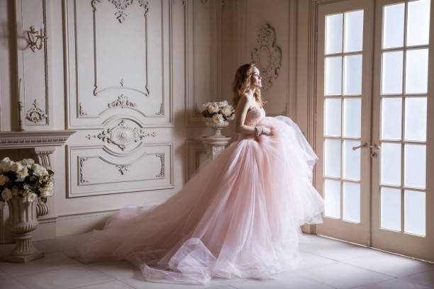 beautiful young blond woman in luxurious long pink dress posing in vintage room interior. - wedding fashion stock pictures, royalty-free photos & images