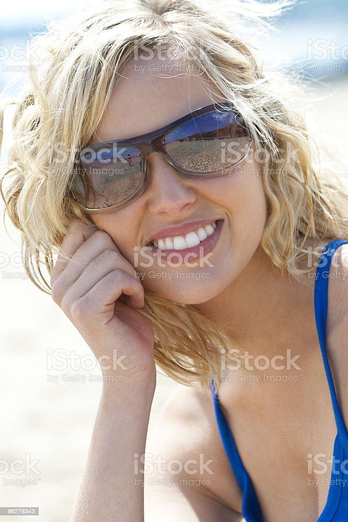 Bellissima giovane donna bionda mette un sorridente in occhiali da sole sulla spiaggia - Foto stock royalty-free di Adulto