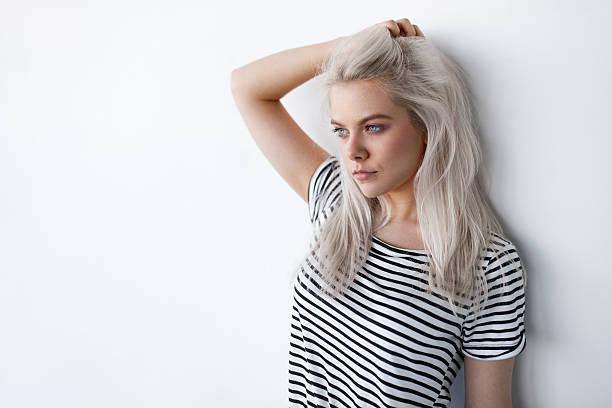 beautiful young blond woman posing while leaning on white wall - capelli ossigenati foto e immagini stock