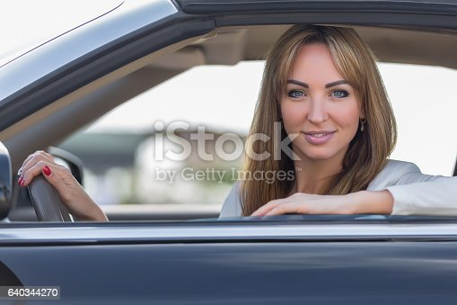 627864748 istock photo Beautiful young blond woman sitting behind wheel of car 640344270