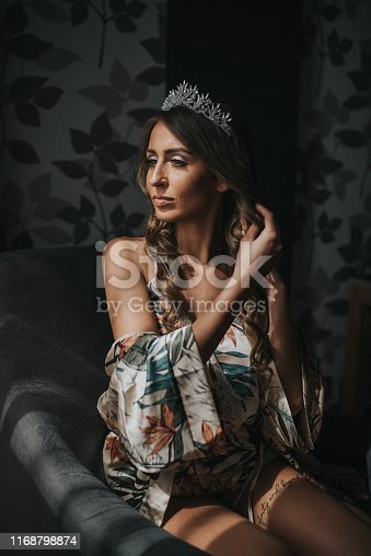 istock Beautiful young blond woman sitting next to the balcony door 1168798874