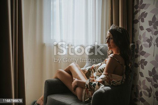 istock Beautiful young blond woman sitting next to the balcony door 1168798875