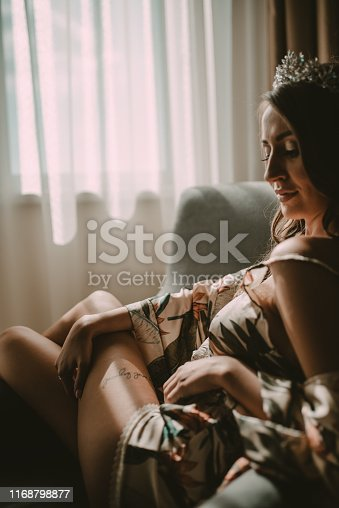 istock Beautiful young blond woman sitting next to the balcony door 1168798877