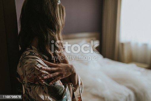 istock Beautiful young blond woman sitting next to the balcony door 1168798878