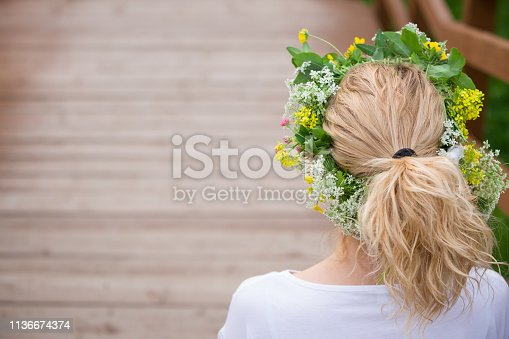 Beautiful young blond woman with flower  wreath on the meadow on a warm summer day. Girl with wild flowers wreath enjoying sun outdoors. Happy woman in the garden. Lifestyle, summer concept