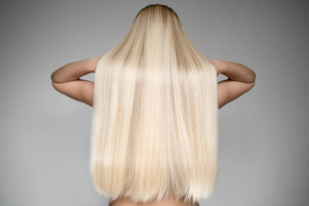 beautiful young blond woman with long straight hair. back view - chica rubia espaldas fotografías e imágenes de stock