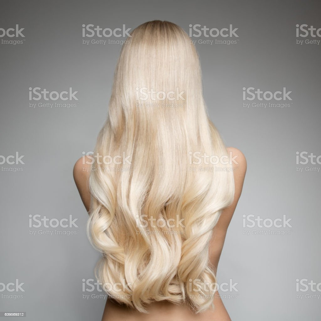 Beautiful Young Blond Woman With Long Wavy Hair. Back view – zdjęcie