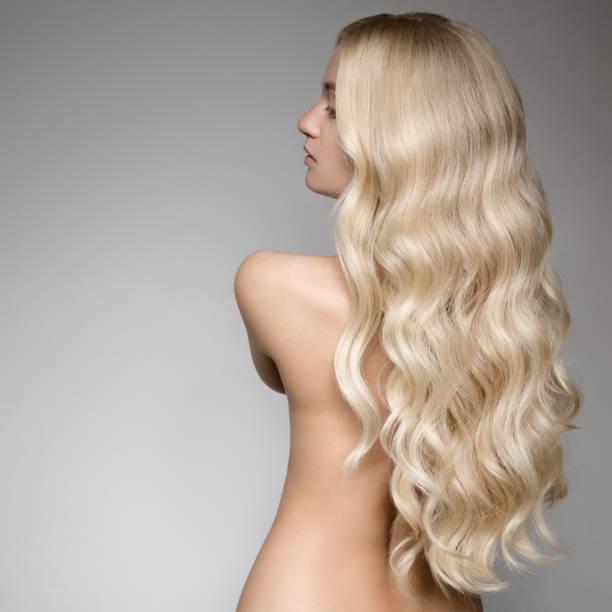 beautiful young blond woman with long wavy hair. back view - chica rubia espaldas fotografías e imágenes de stock
