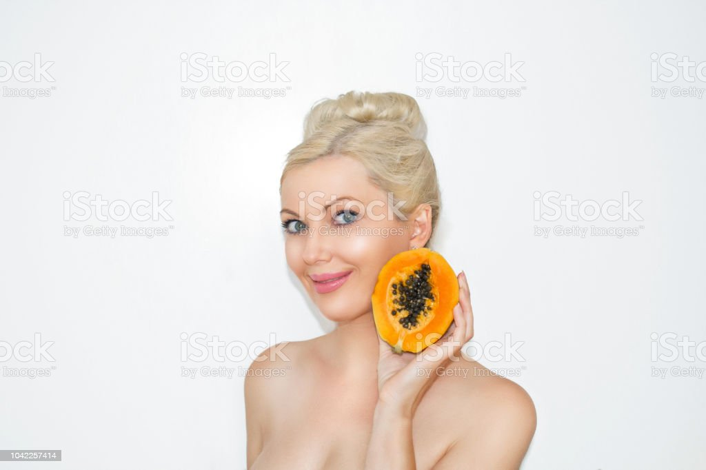 Beautiful young blond woman with papaya in hands. The concept of healthy skin and moisturizing. Advantages of fruit. stock photo