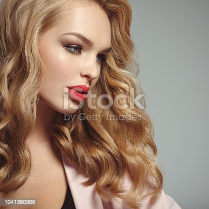 Profile portrait of a beautiful young blond woman with sexy red lips.  attractive girl with long curly hair. Smoky eye makeup