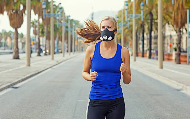 Beautiful young blonde athletic female running in daytime sunny surroundings stock photo