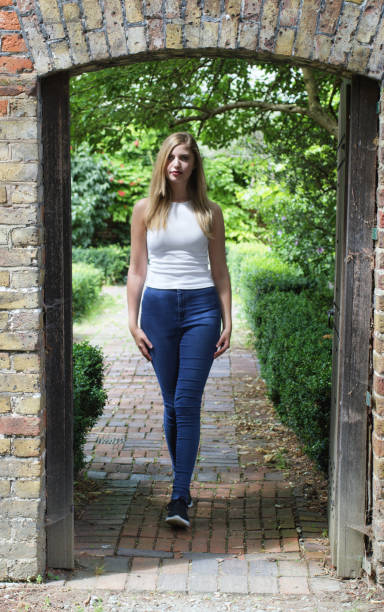 beautiful young blonde bulgarian outdoor girl in doorway to walled garden - whiteway english outdoor girl stock photos and pictures
