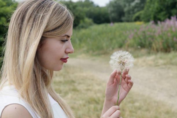 beautiful young blonde bulgarian outdoor girl touching soft goatsbeard seeds - whiteway bulgarian outdoor girl stock photos and pictures