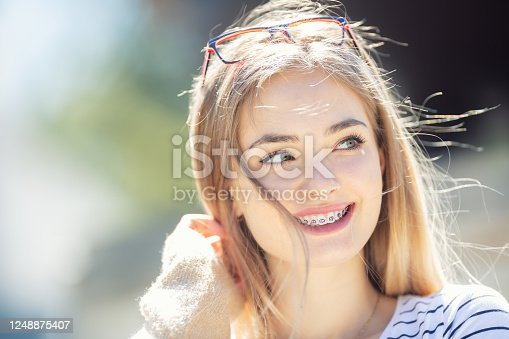 Beautiful young blonde girl wearing dental braces, smiling and looking to the side.