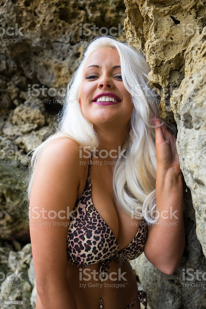 Beautiful young blonde haired woman in bikini against rocks smil stock photo