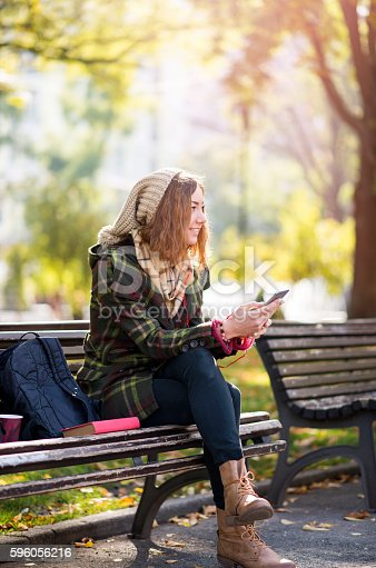 istock Beautiful young blonde hipster woman listening music 596056216