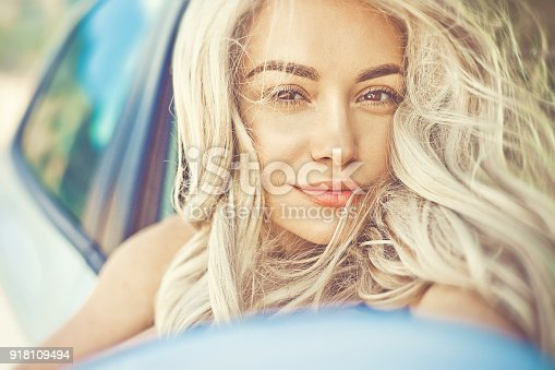 istock Beautiful young blonde in car on the beach 918109494